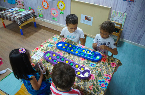 Playing the traditional game, Congkak, in its original form and in modified preschool-level version