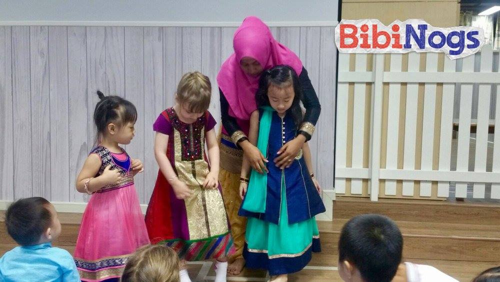 The teacher showcases and describes different types of traditional Indian costumes