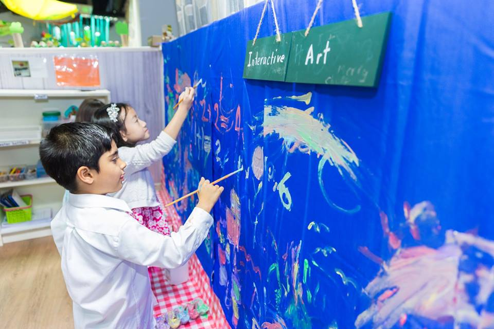 Children contributing in their own ways to the interactive art wall